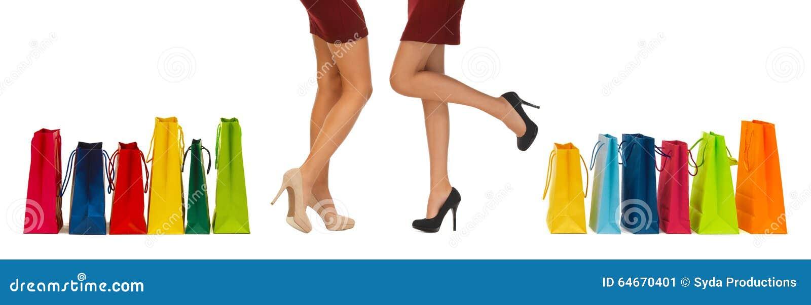 Fermez-vous des femmes sur des talons hauts avec des paniers