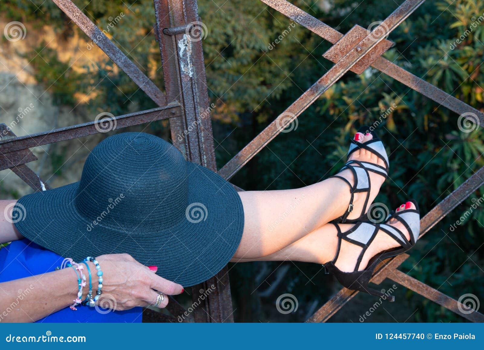 Fermez-vous des jambes femelles avec un chapeau débordé large du ` s de femmes de couleur