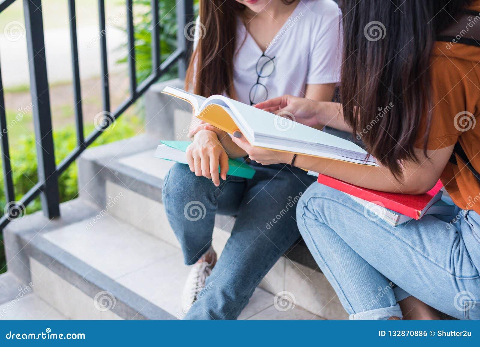 Fermez-vous des livres asiatiques FO de lecture et de soutien scolaire de deux filles de beauté