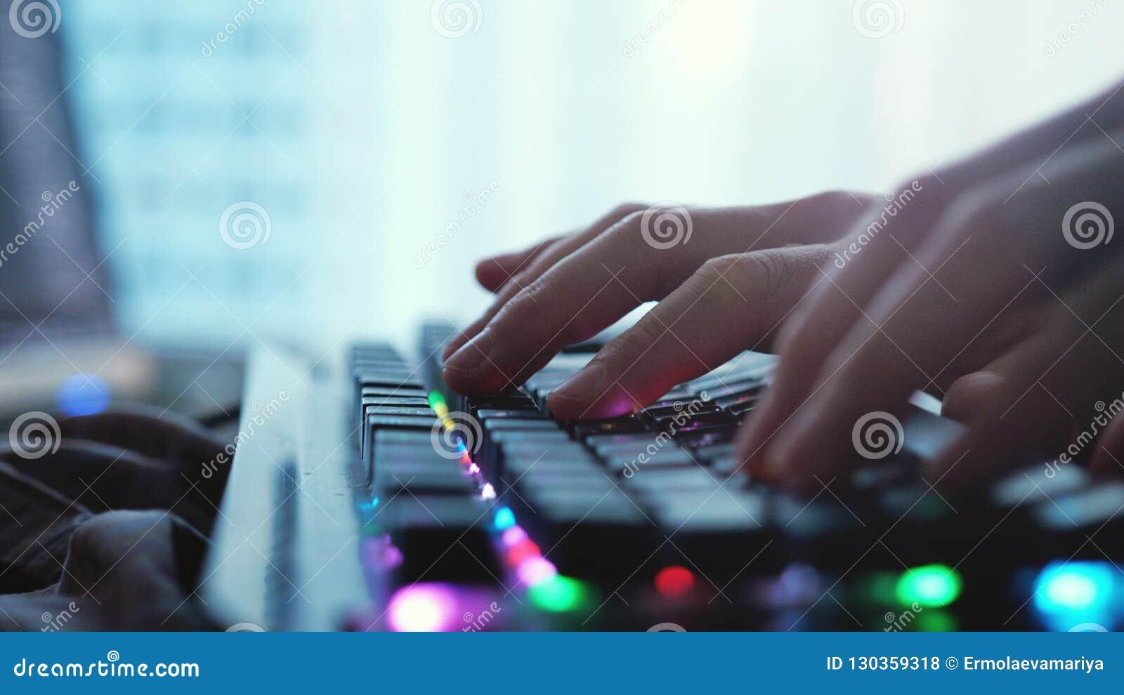Fermez-vous des mains masculines dactylographiant sur un clavier d ordinateur portable par la fenêtre panoramique
