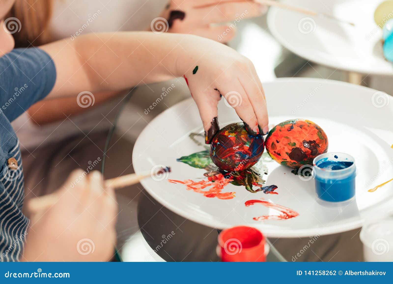 Fermez-vous des oeufs de peinture caucasiens de femme et d enfant, en se préparant à Pâques