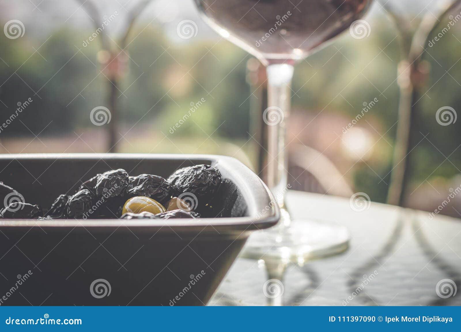 Fermez-vous des olives en cuvette noire et vin rouge en verre de vin sur la table