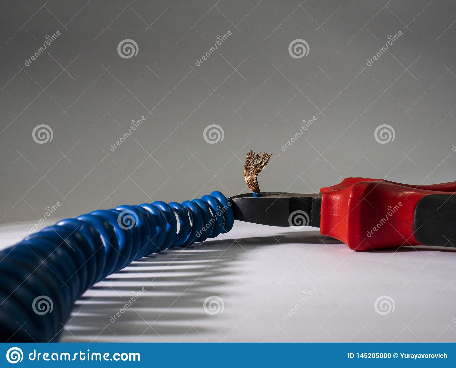 Fermez-vous des pinces rouges et du fil tordu bleu sur le fond blanc Pinces coupant le câble