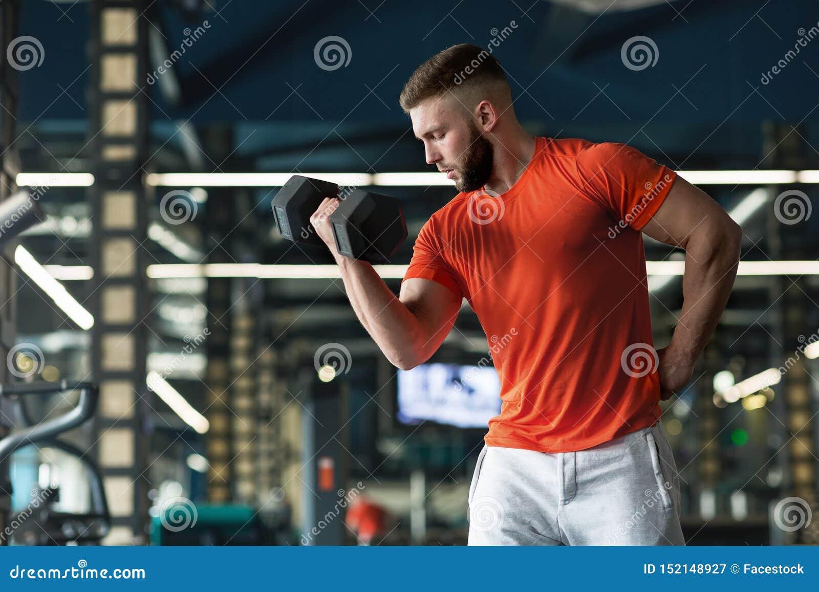 Fermez-vous du bodybuilder tenant une haltère et l établissant dans le gymnase