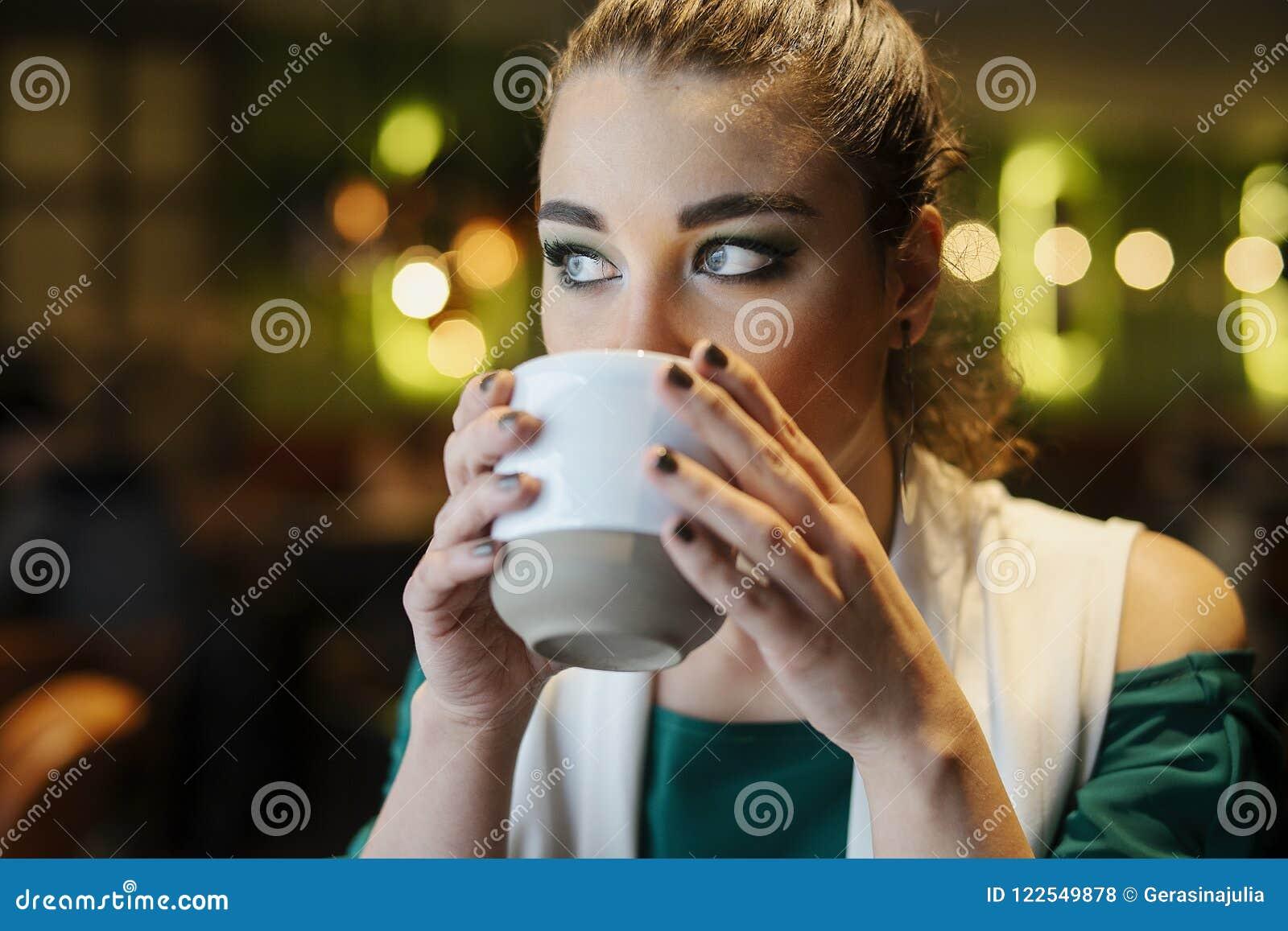 Fermez-vous du café potable de jeune femme de brune