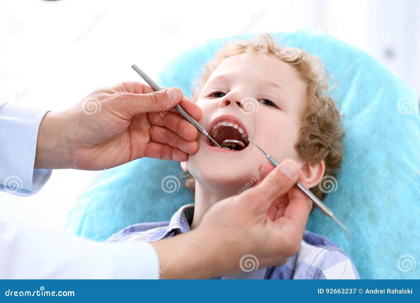 Fermez-vous du garçon faisant examiner ses dents par un dentiste