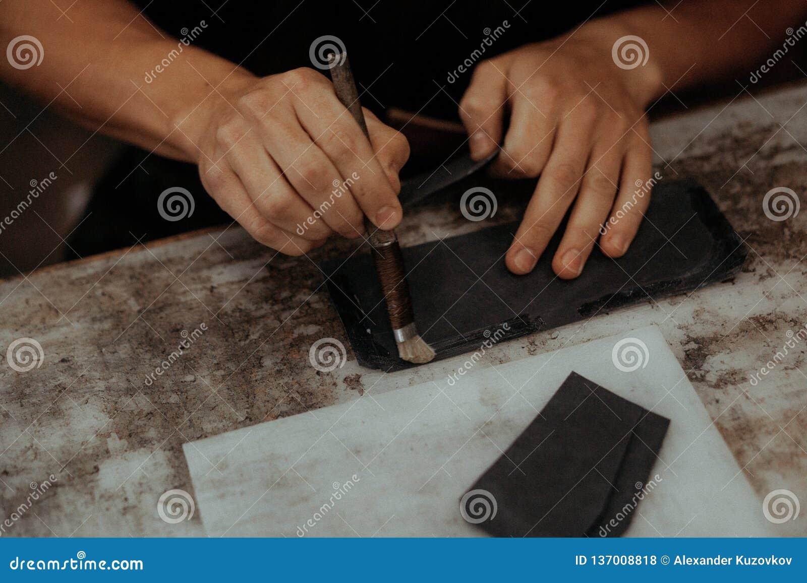 Fermez-vous du maître faisant le portefeuille en cuir avec la brosse et la colle Maître fait main au travail dans l atelier local