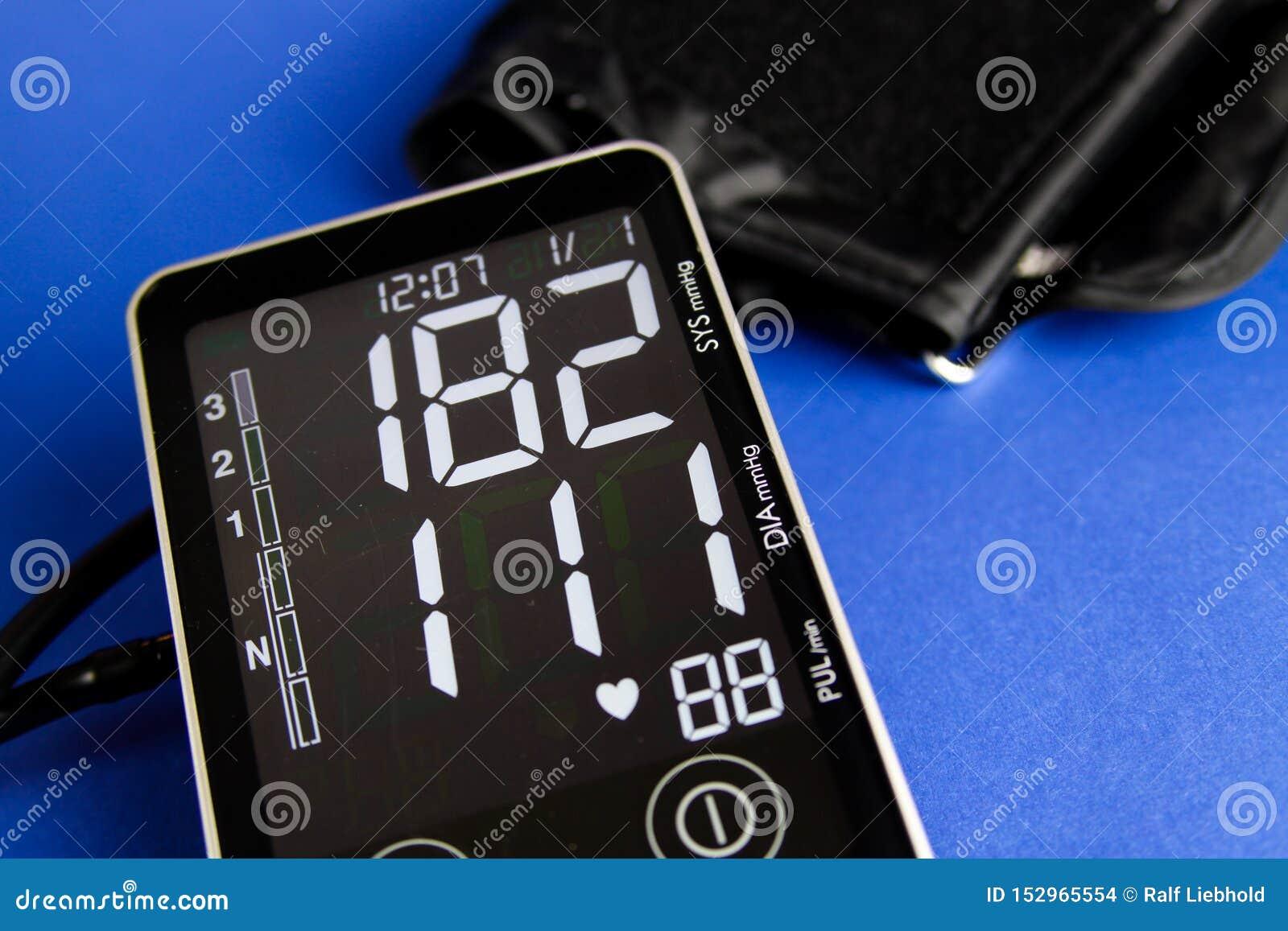 Fermez-vous du moniteur numérique de sphygmomanometer avec la manchette montrant la tension artérielle diastolique et systolique