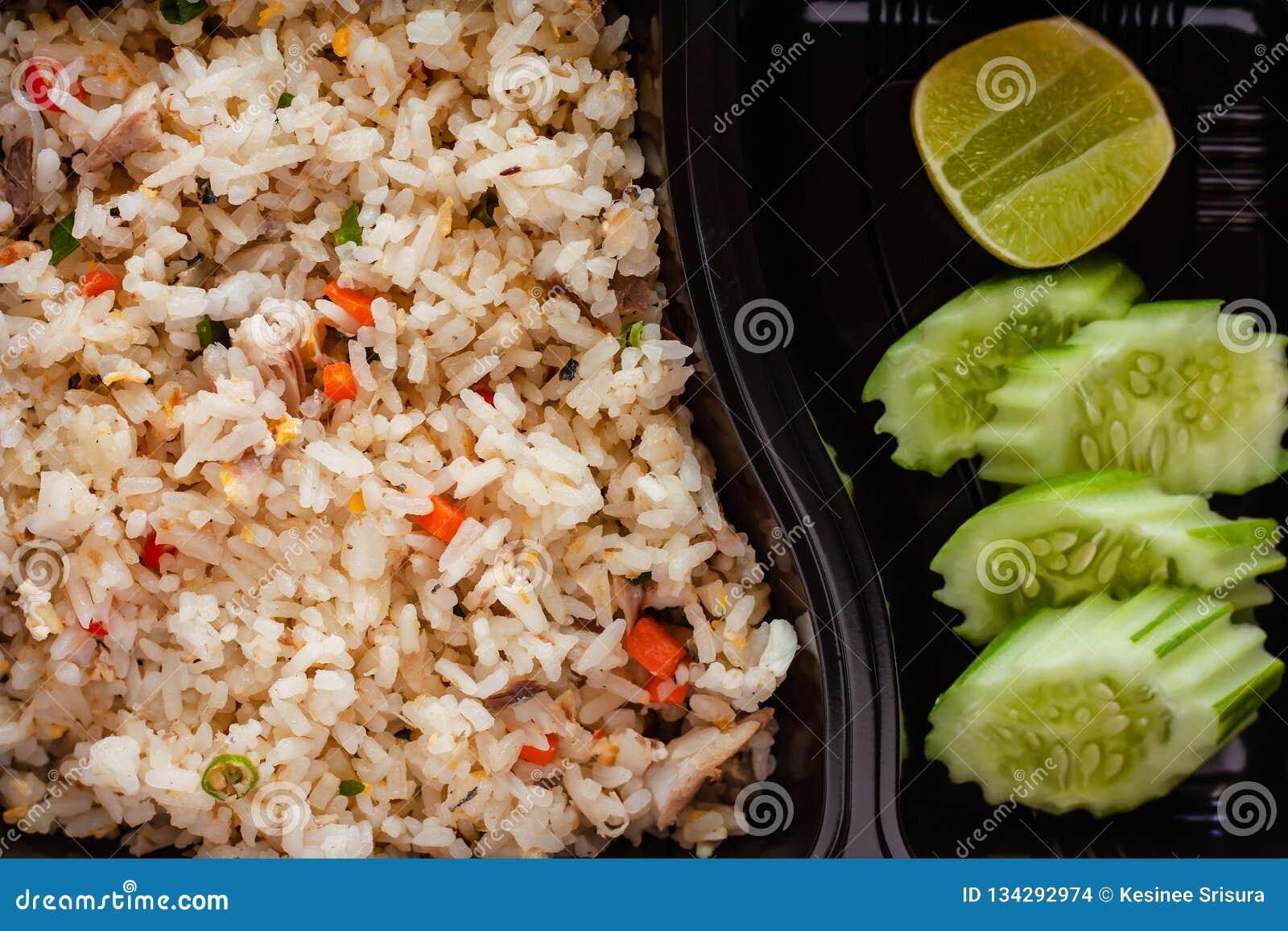Fermez-vous du riz frit délicieux avec le concombre et le citron du côté dans la gamelle