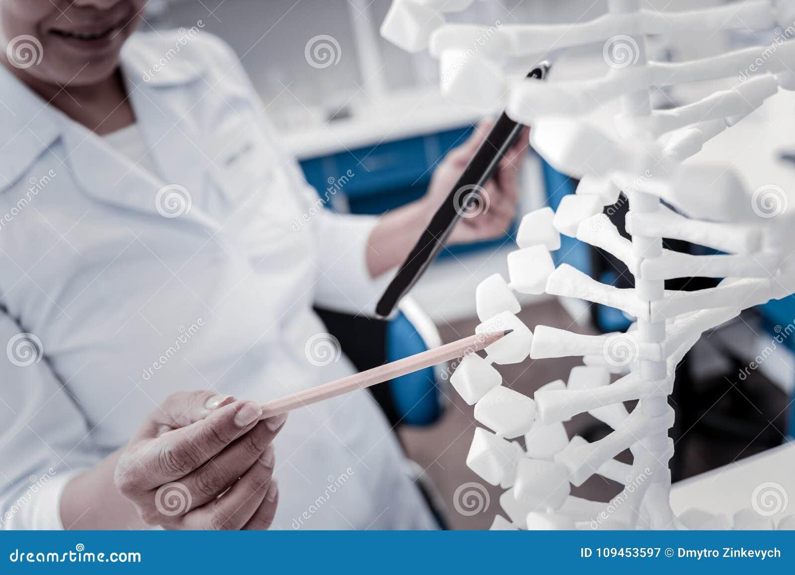 Fermez-vous du scientifique féminin analysant le modèle d ADN