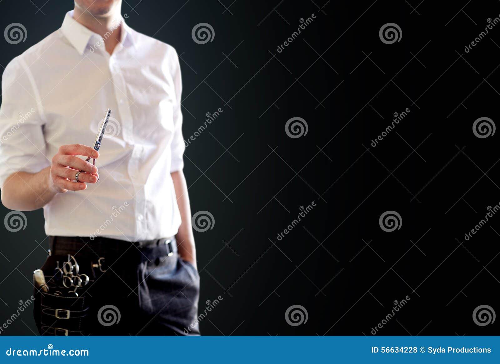 Fermez-vous du styliste masculin avec des ciseaux au-dessus de noir