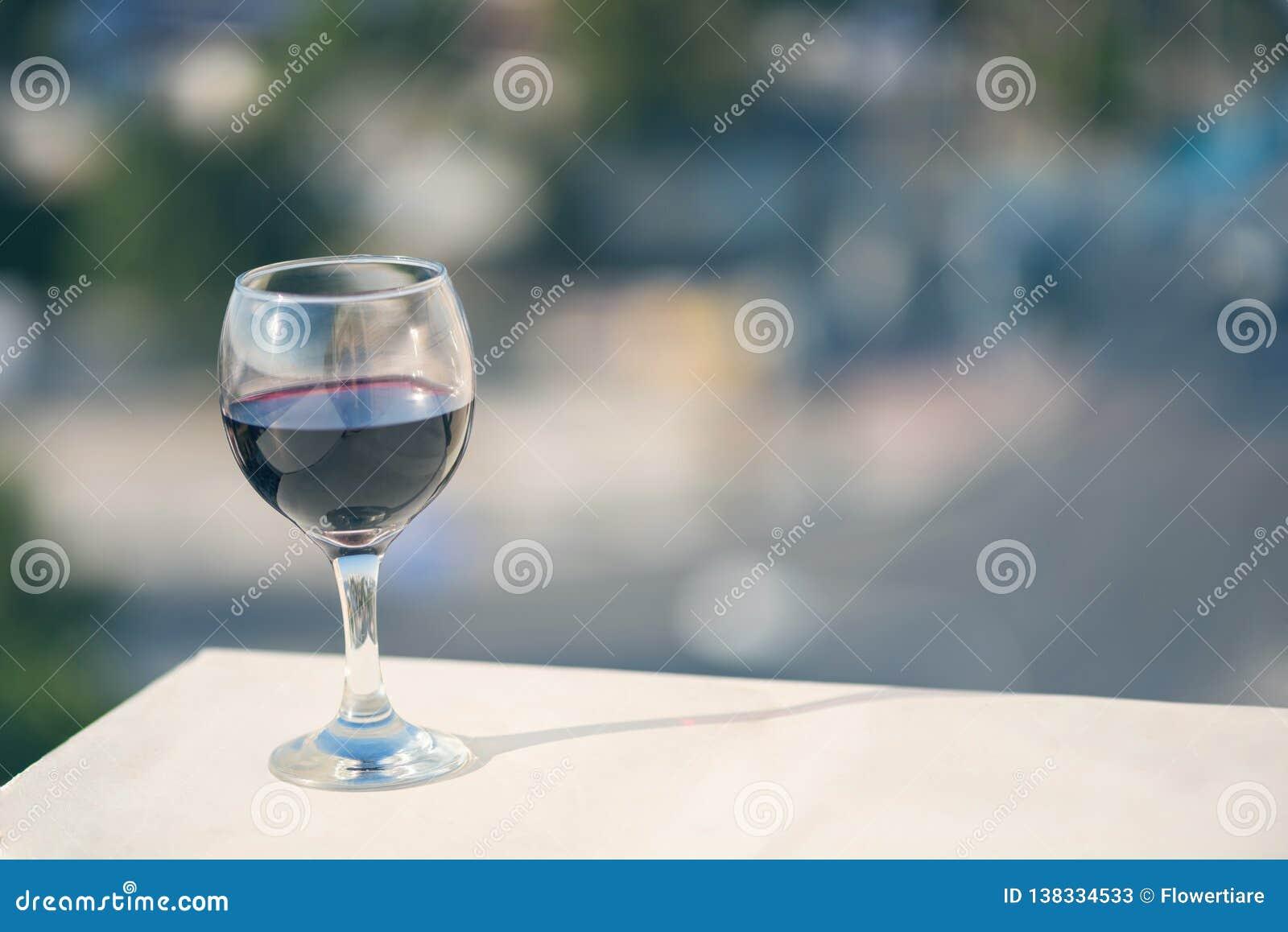 Fermez-vous du verre de vin rouge dans la perspective de la ville brouillée avec le bokeh