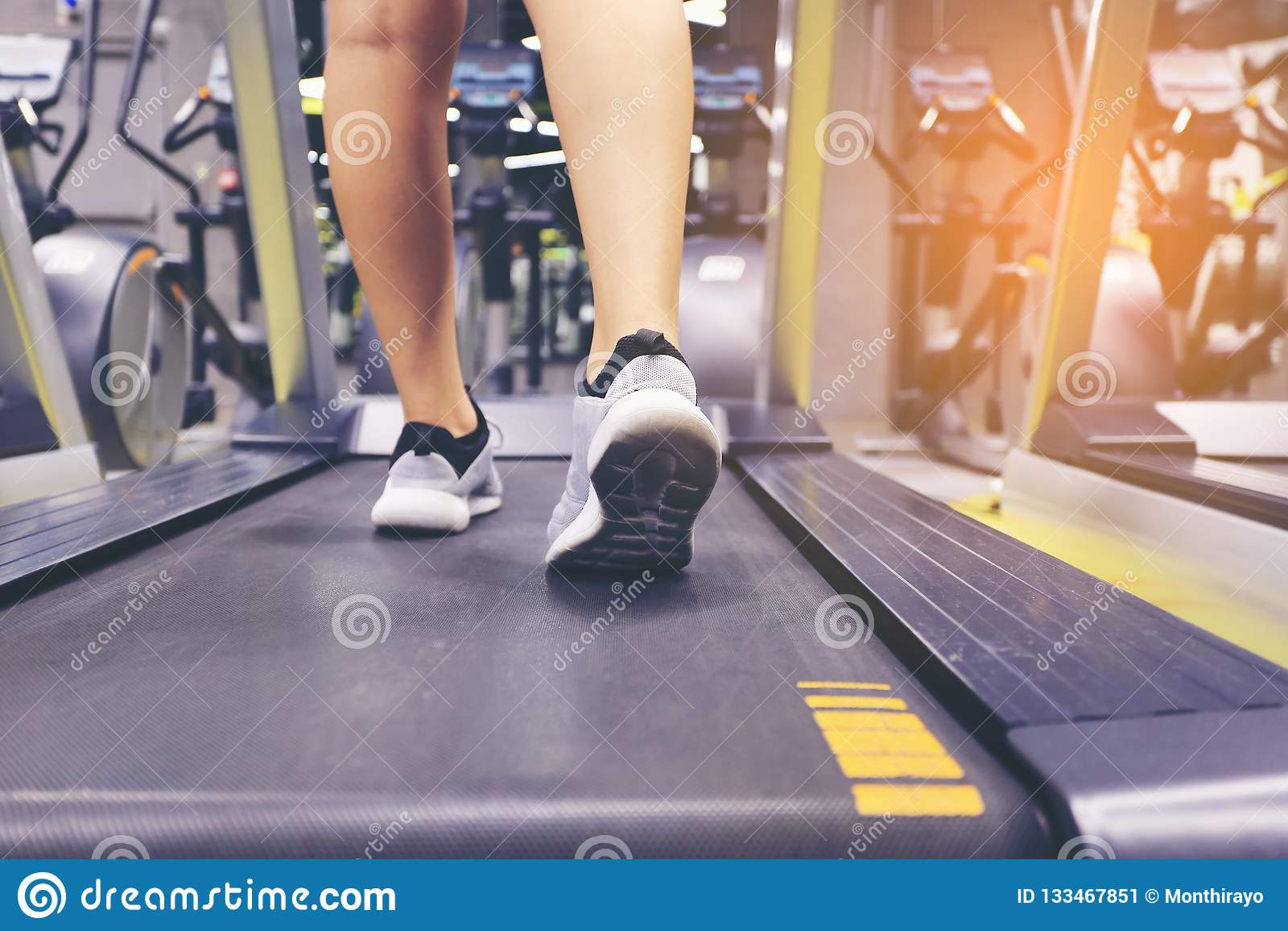 Fermez-vous sur des jambes de chaussure, de femme de forme physique fonctionnant sur le tapis roulant et des Bu