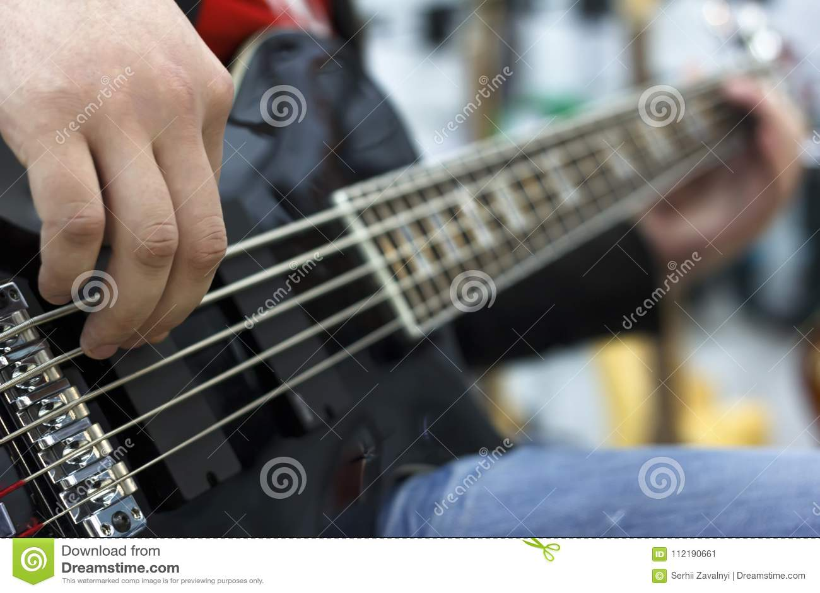 Fermez-vous sur les doigts du musicien jouant la guitare basse sur l étape