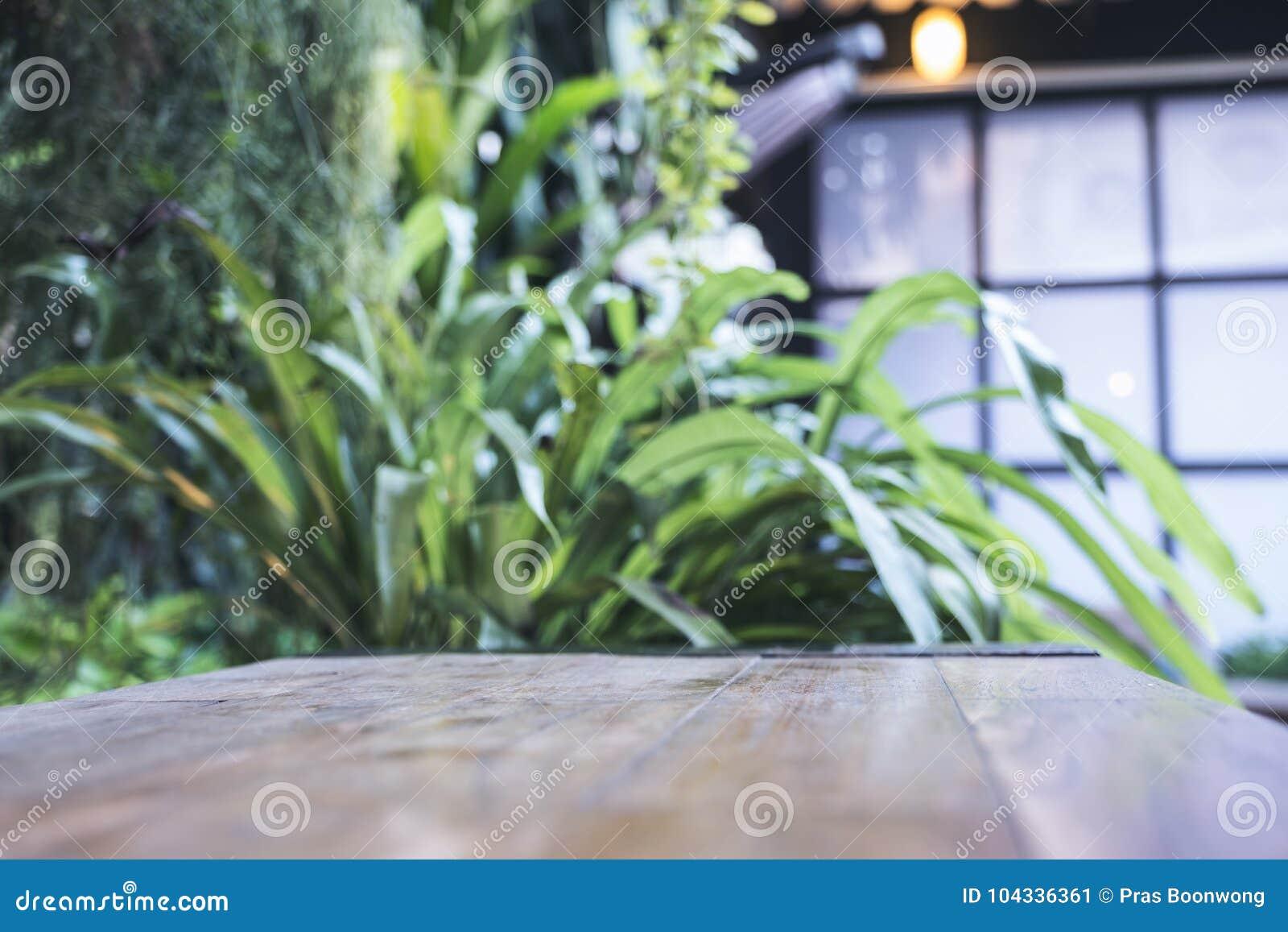 Fermez-vous vers le haut de l image d une table en bois avec le bokeh de tache floue de la nature verte