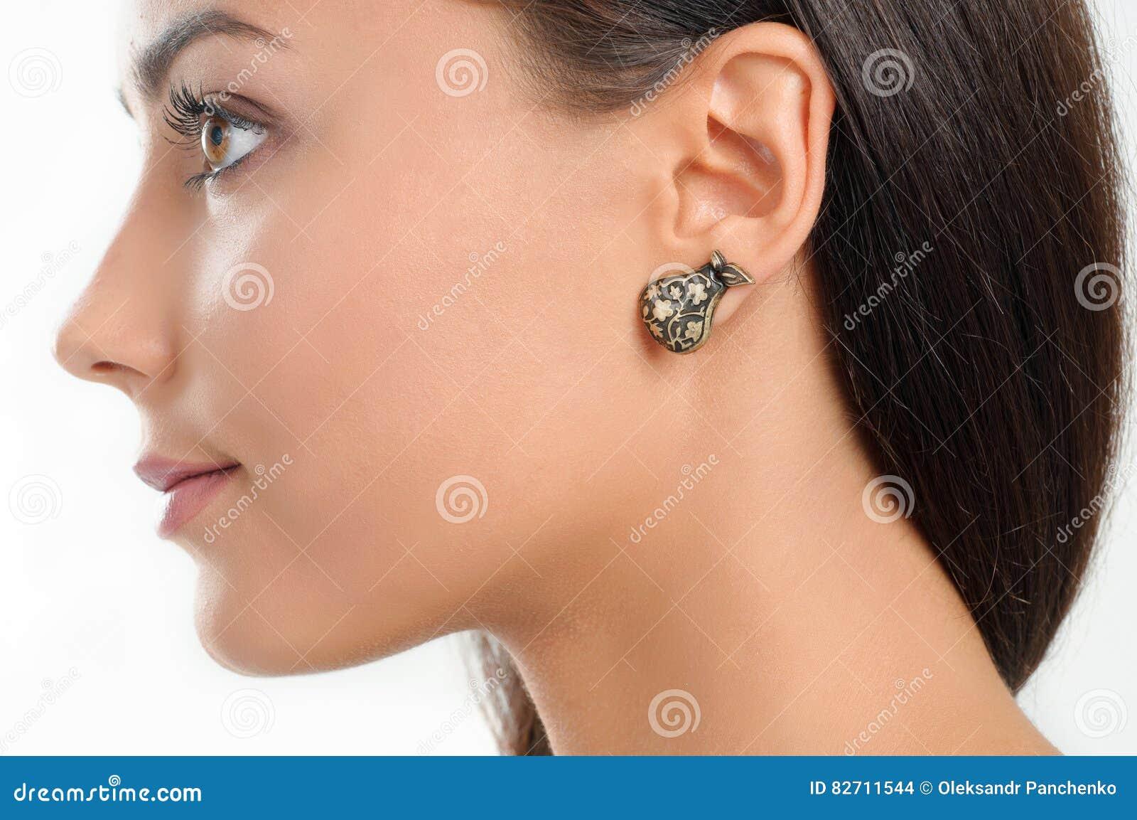Fermez-vous vers le haut de la beauté de portrait avec la boucle d oreille élégante et le long hai brun