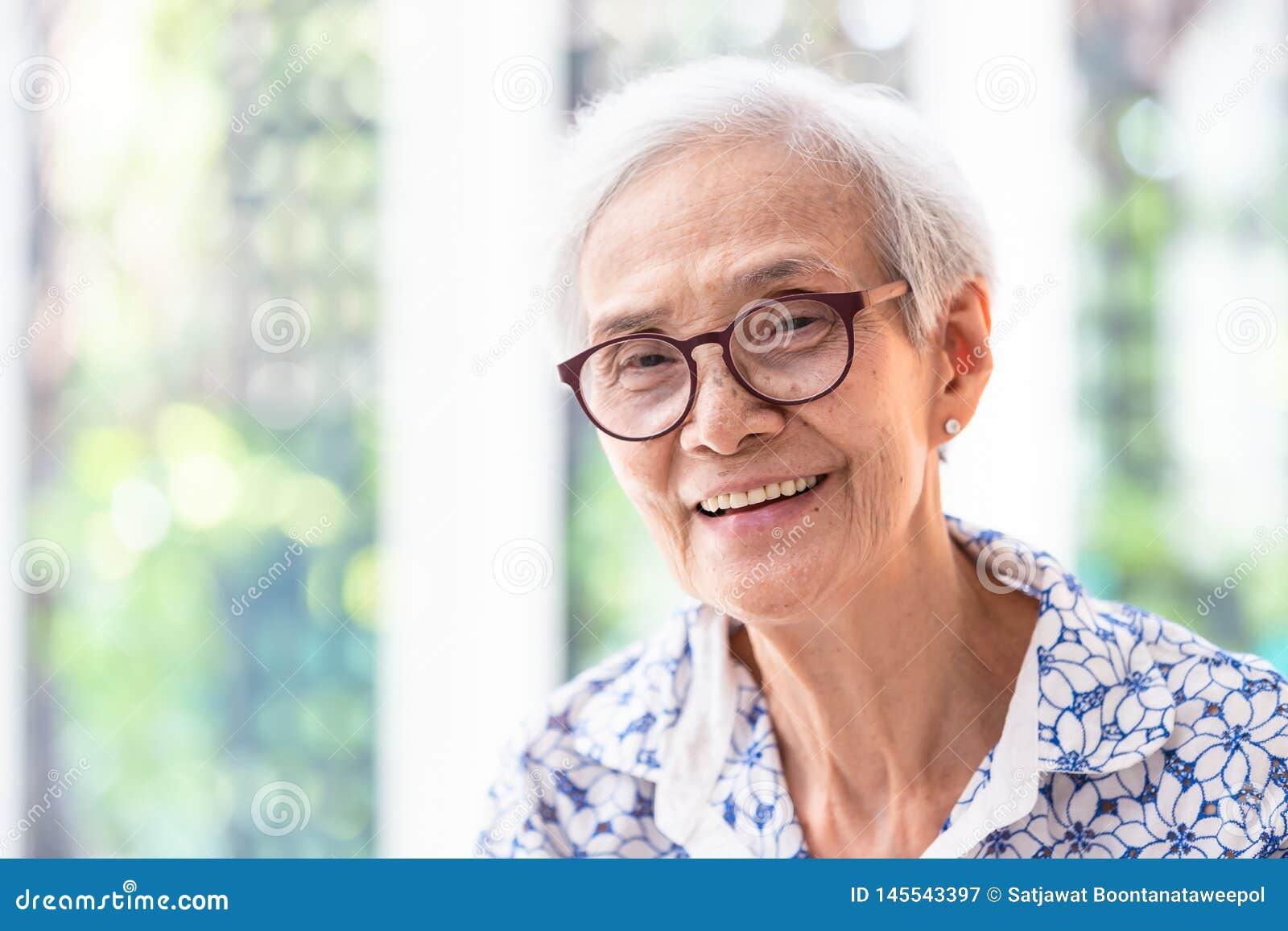 Fermez-vous vers le haut de la femme agée asiatique en verres montrant les dents droites saines, sentiment de sourire de femme su