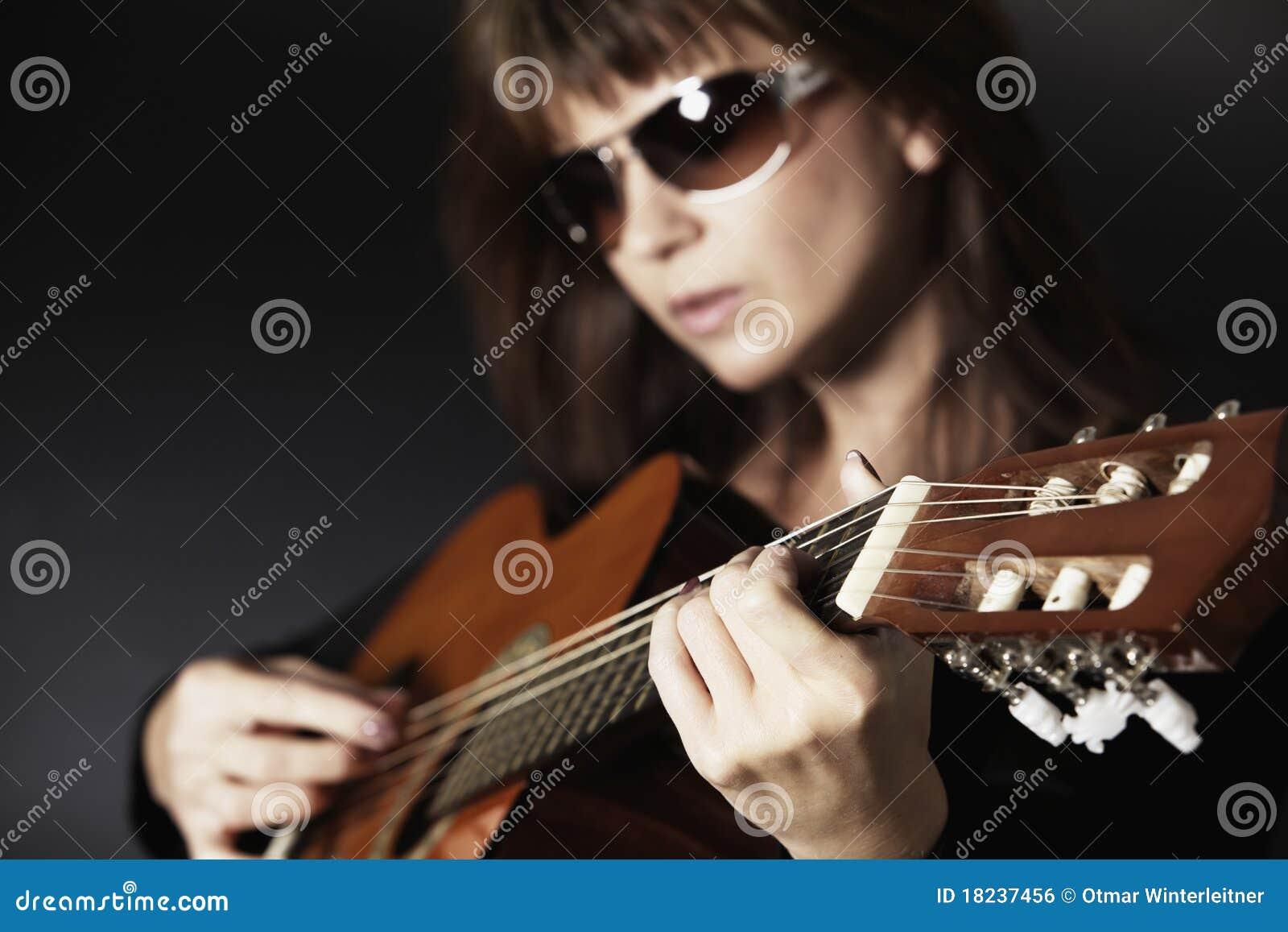 Fermez-vous vers le haut de la main de la fille jouant la guitare.