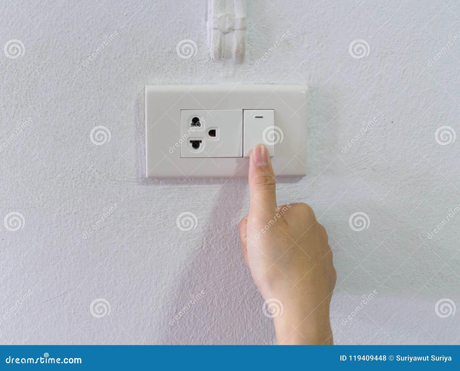 Fermez-vous vers le haut de la main femelle tournant  Marche/Arrêt  sur l interrupteur de lampe gris avec