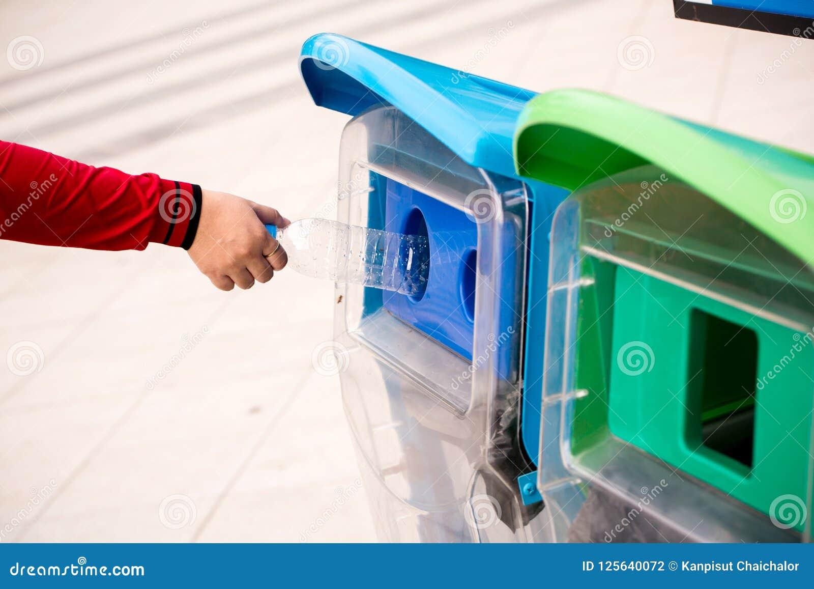 Fermez-vous vers le haut de la main de foyer sélectif jetant la bouteille en plastique vide dans les déchets Main de femme mettan