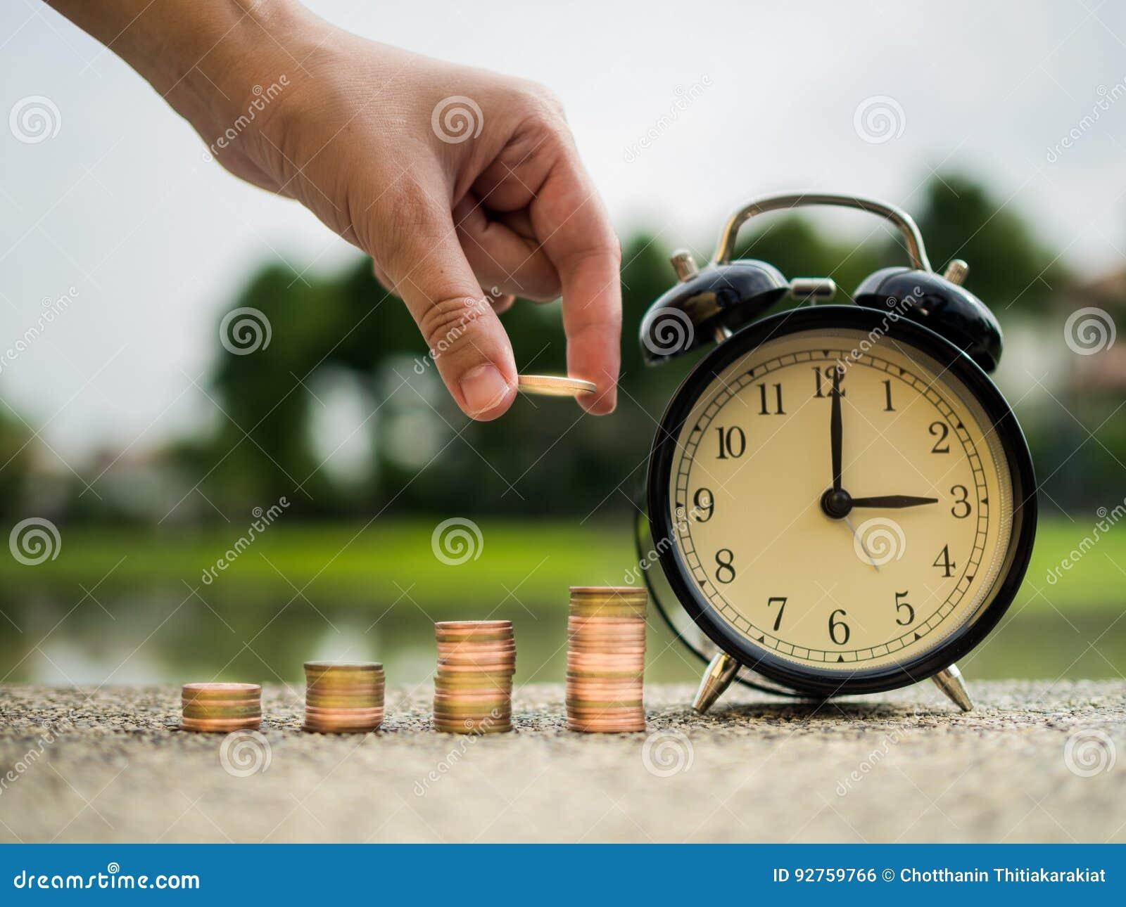 Fermez-vous vers le haut de la main mettant l argent à la pile de pièces de monnaie avec du temps, valeur temps de concept d arge