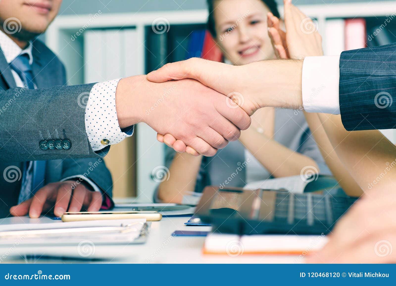 Fermez-vous vers le haut de la poignée de main d affaires sur la réunion d équipe avec le groupe de personnes de applaudissement