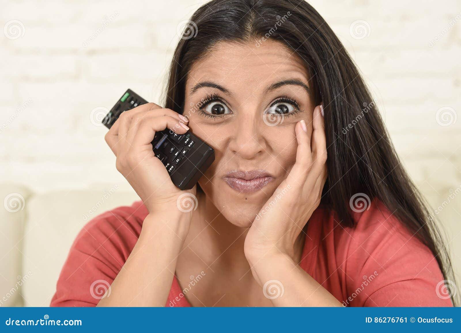 Fermez-vous vers le haut de la télévision de observation à la maison de jeune belle femme espagnole de portrait sur enthousiaste
