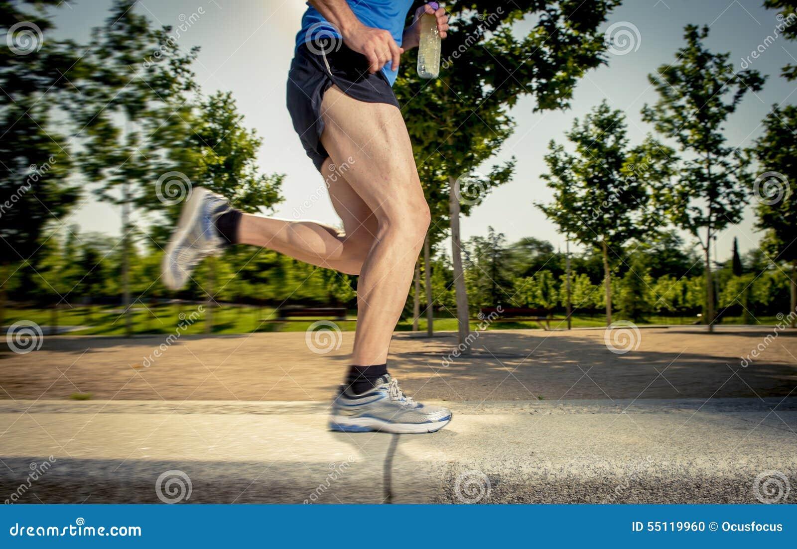 Fermez-vous vers le haut des jambes sportives du jeune homme fonctionnant en parc de ville avec des arbres sur le mode de vie sai