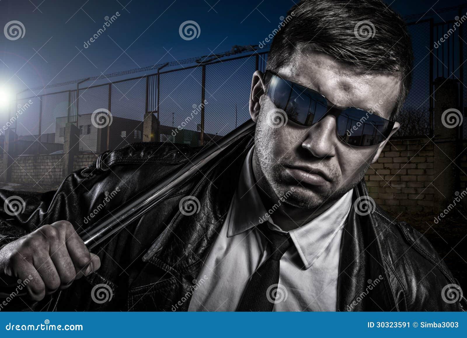 Fermez-vous vers le haut du portrait de l homme dangereux secret élégant avec le bâton en acier