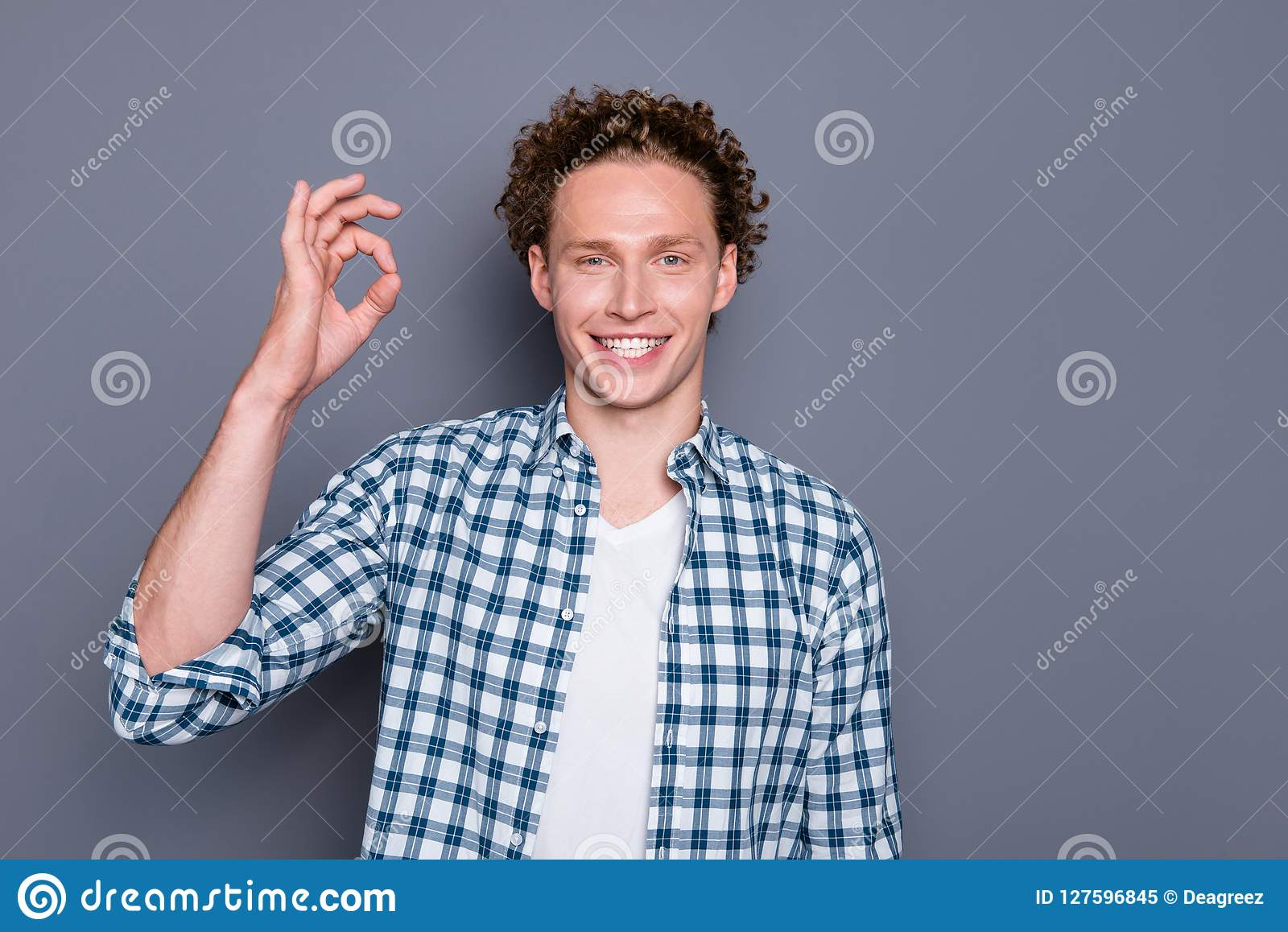 Fermez-vous vers le haut du type beau frais ofsatisfied par portrait de photo faisant le fond correct de gris de symbole