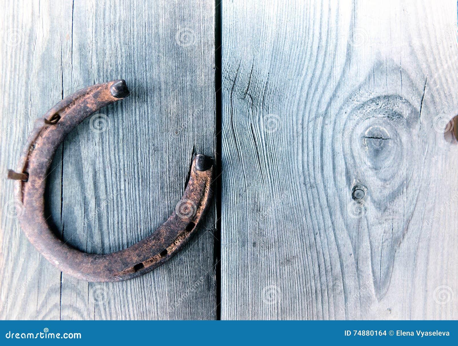 Ferradura oxidada velha na placa de madeira do vintage