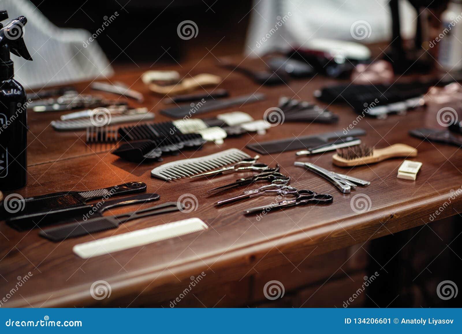 Ferramentas do barbeiro na tabela de madeira Acessórios para a rapagem e os cortes de cabelo