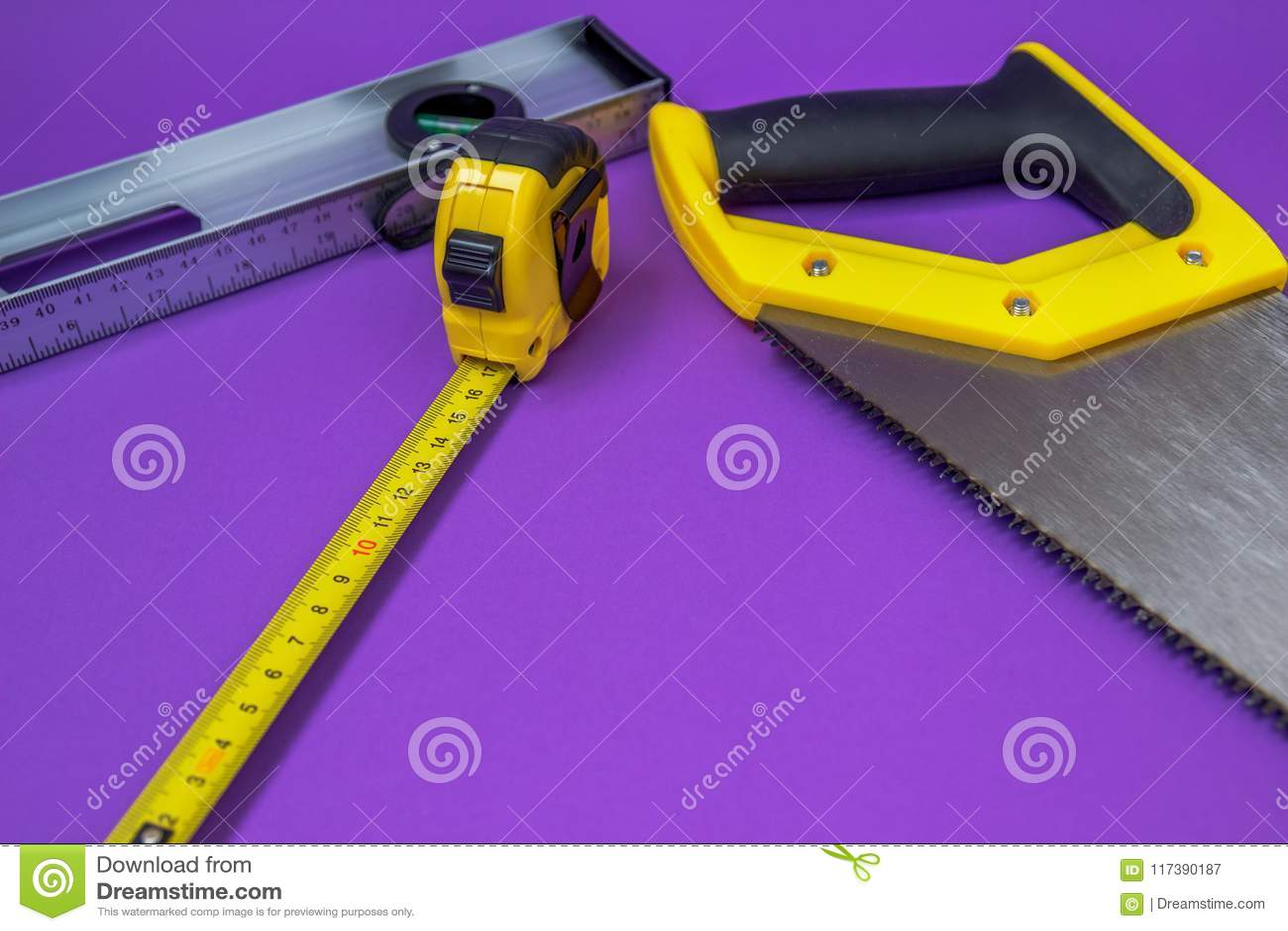 Ferramentas serra de madeira amarela da mão, grampeador, fita métrica