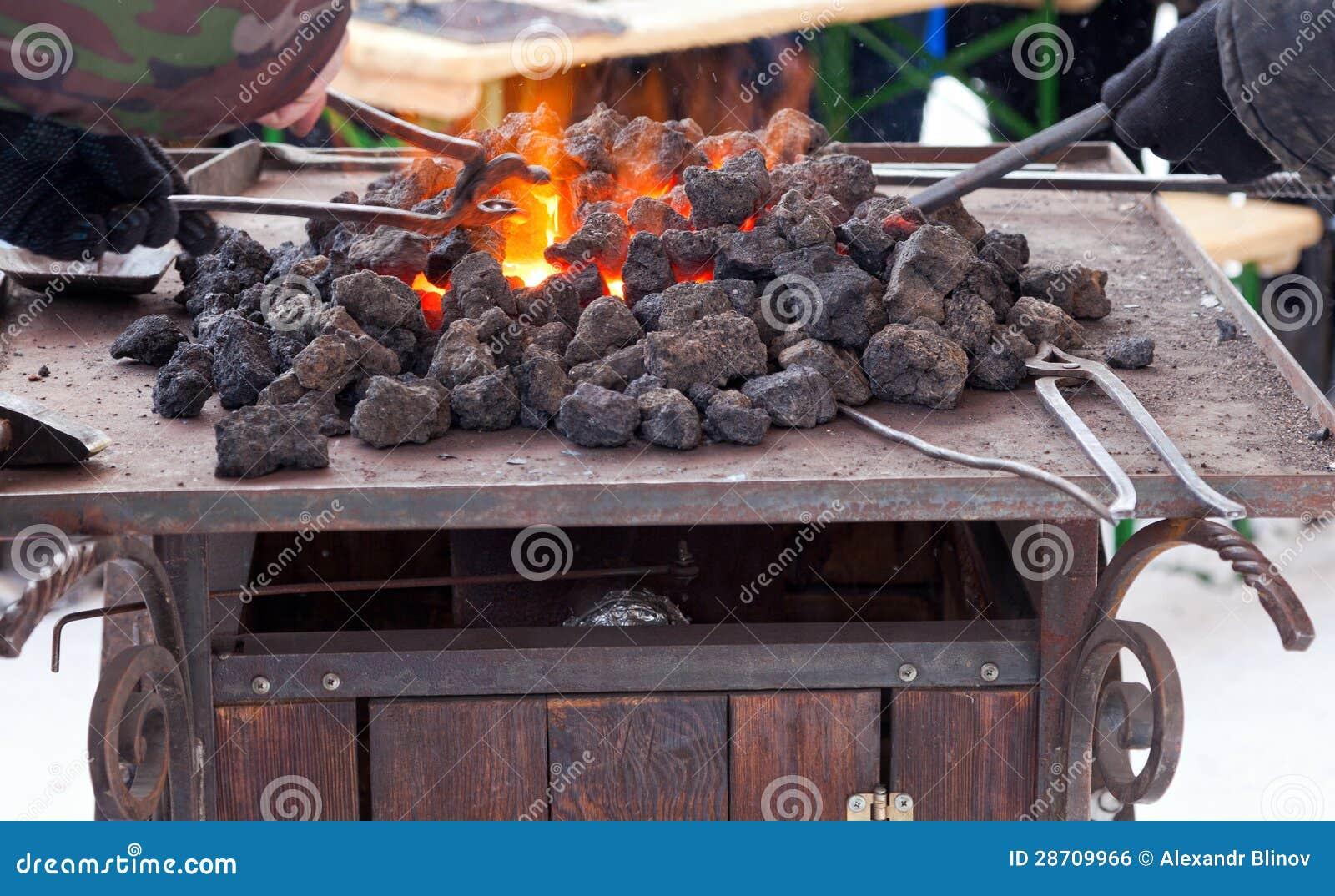 Ferreiro do artesão que aquece uma parte de ferro