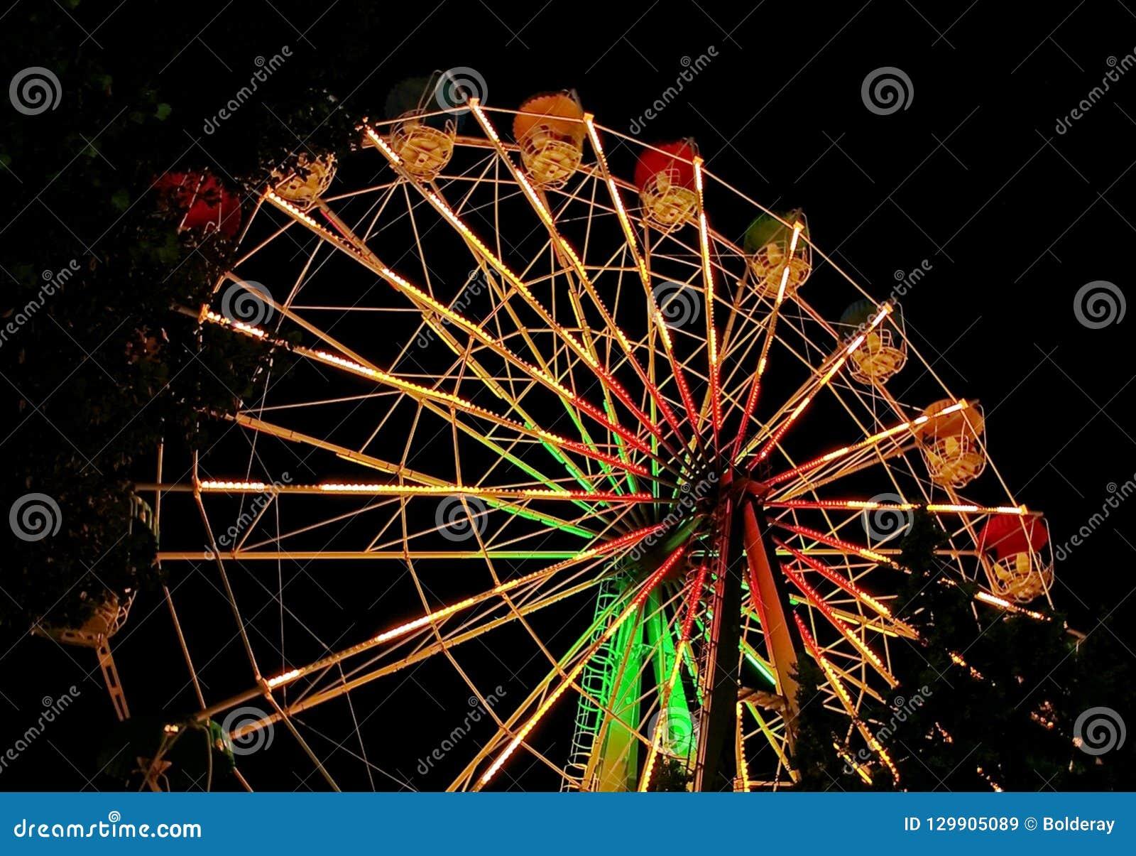 Ferris wheel against the background of the night sky. Night illumination ferris wheel.