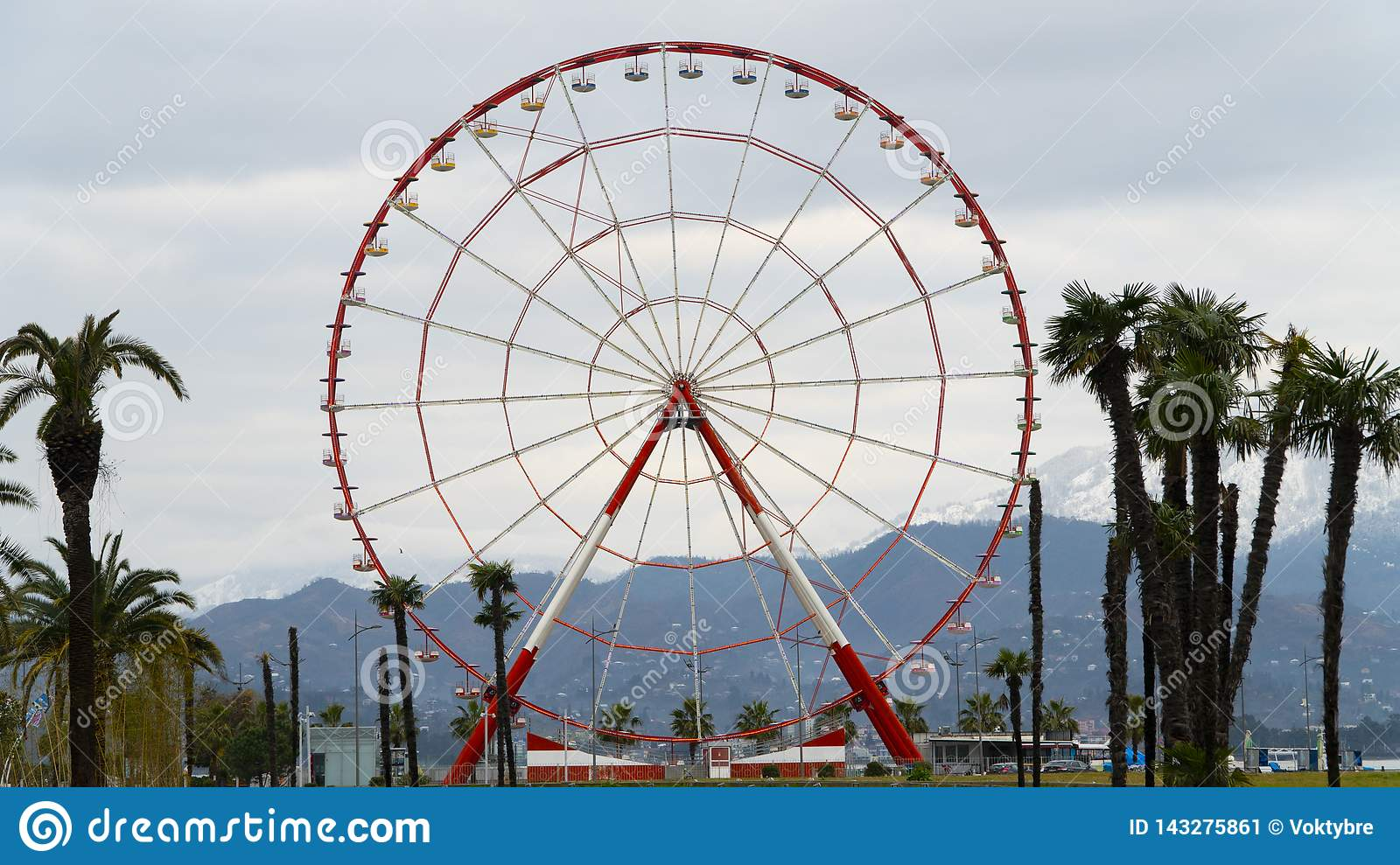 Ferris wheel on the coast of the Black Sea in Batumi on the background of mountains
