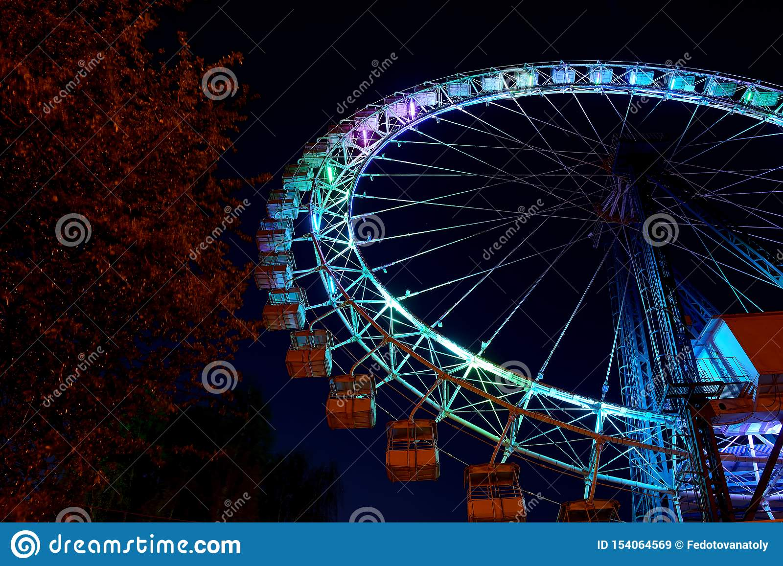 Ferris wheel with blue lighting and trees at night