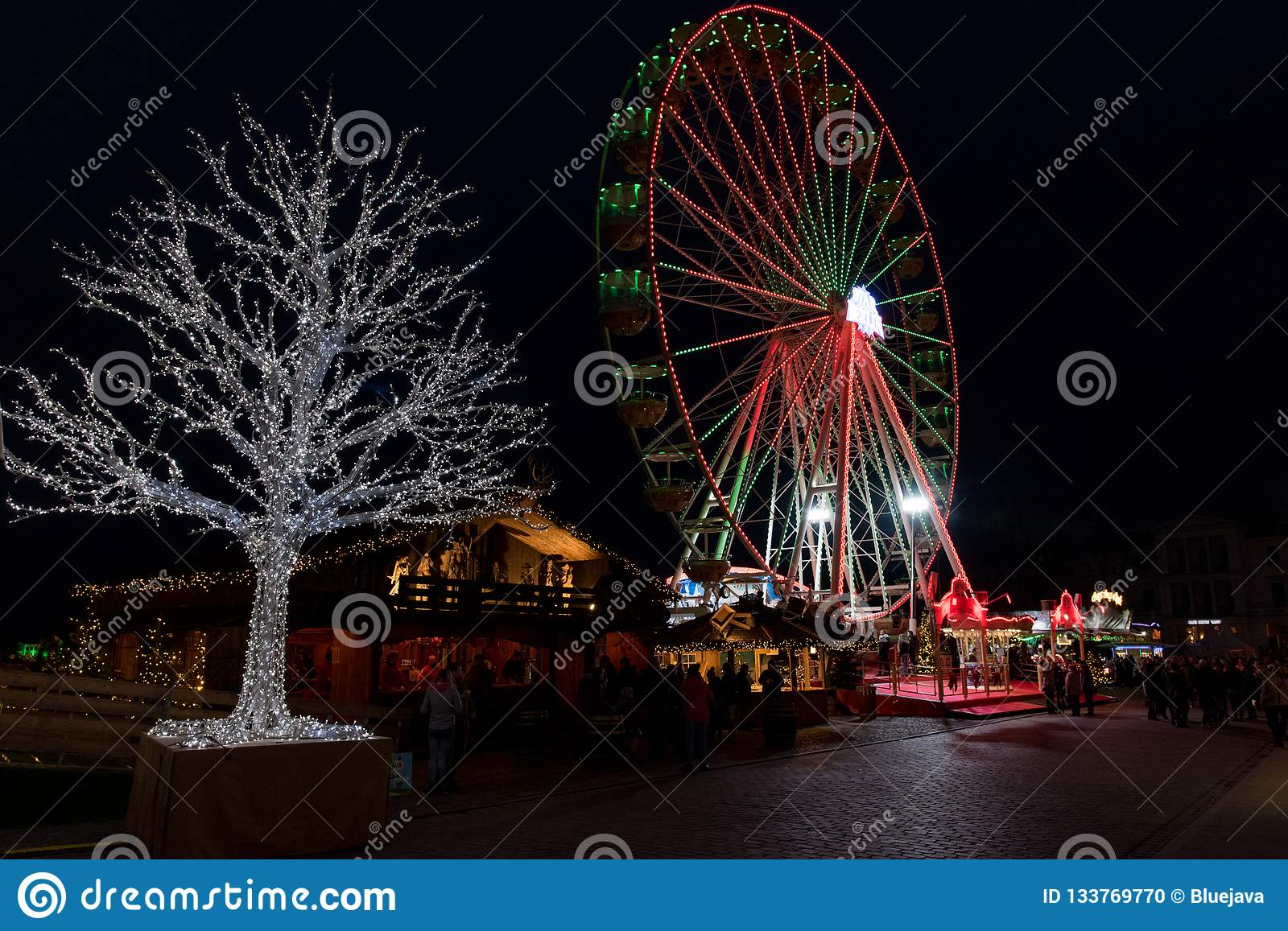 Ferris wheel and tree in lots of light at the christmas fair in