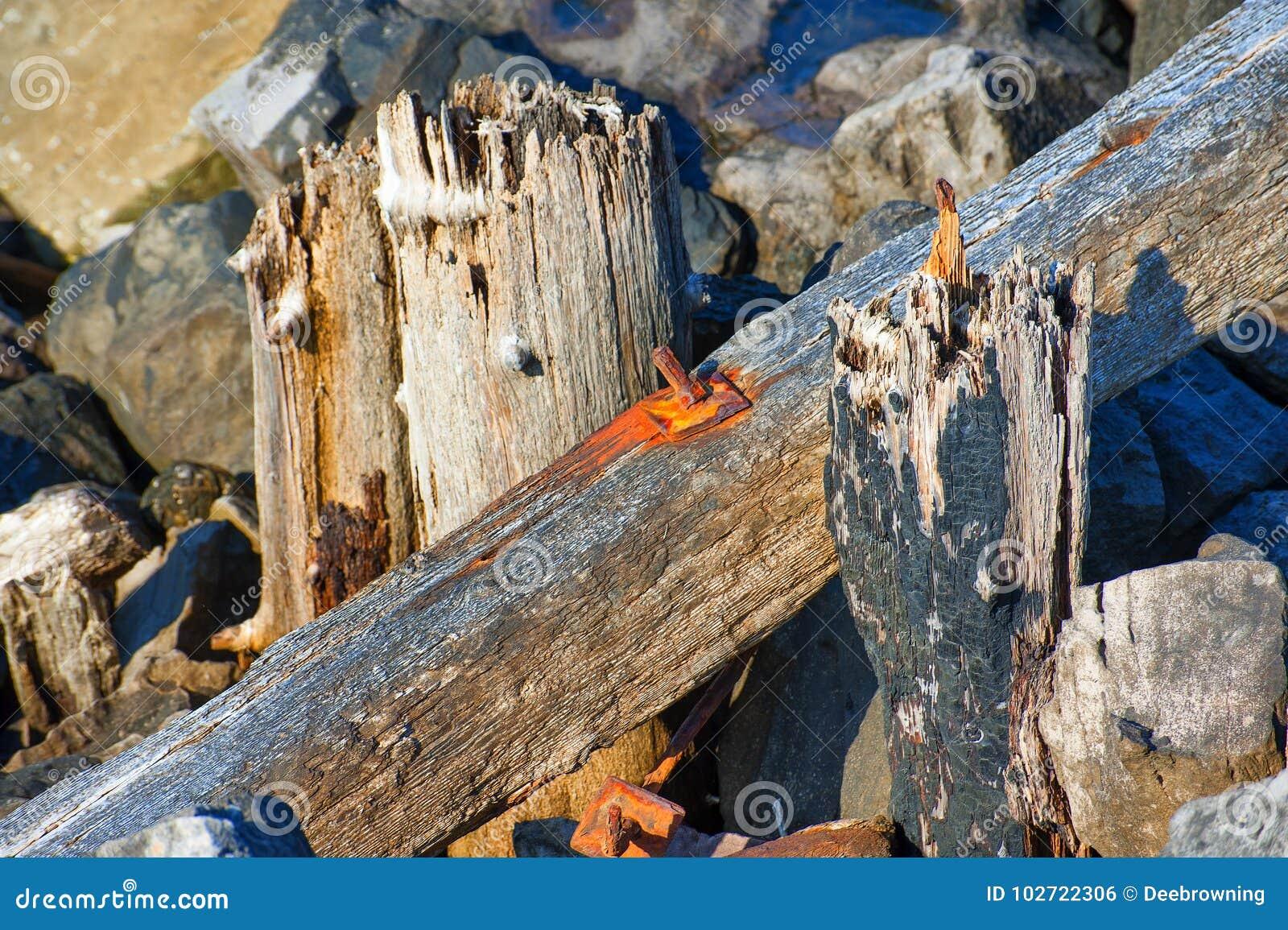 Ferro oxidado encaixado na madeira ao longo do molhe sul