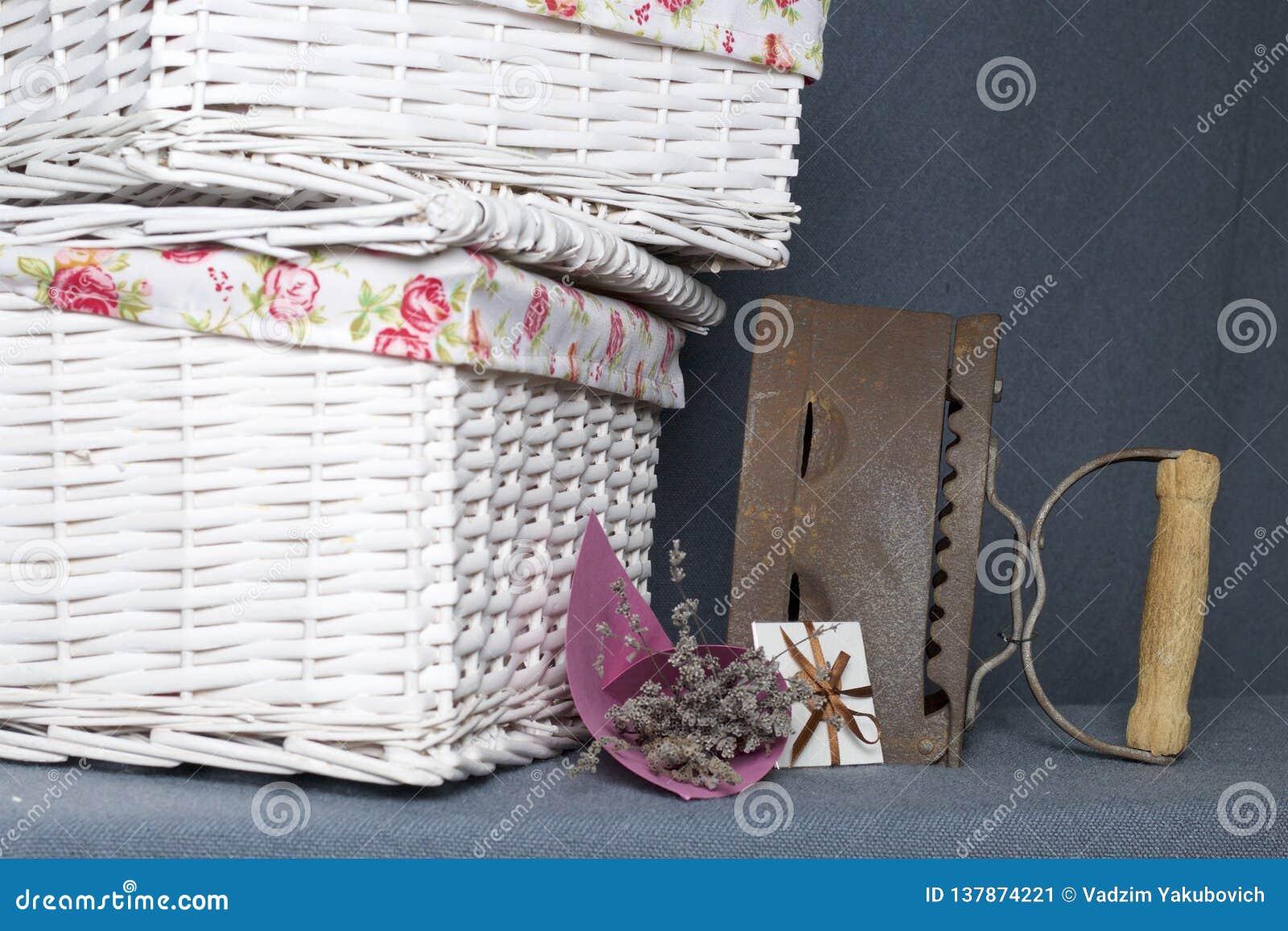 Ferro velho, aquecido por carvões quentes Localizado na tela cinzenta Estão próximo as cestas de vime, um ramalhete de flores sec