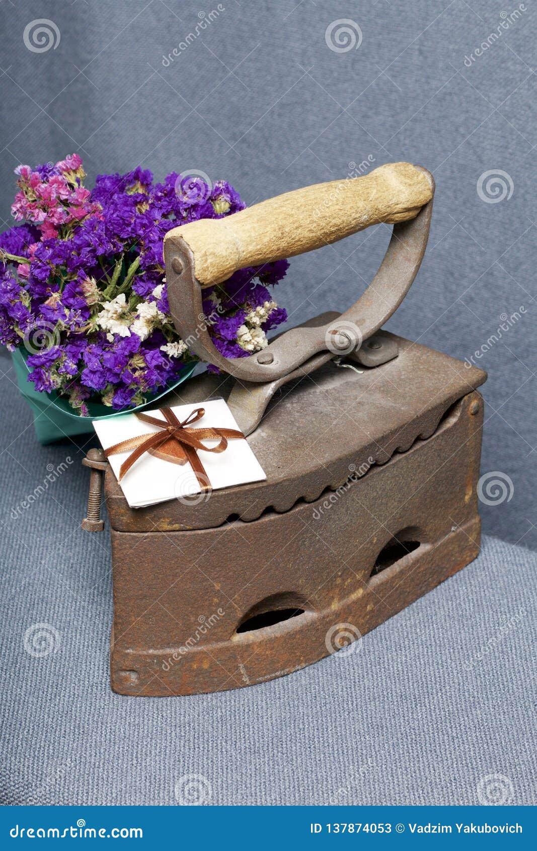 Ferro velho, aquecido por carvões quentes Localizado na tela cinzenta Estão próximo o ramalhete de flores secadas e um cartão