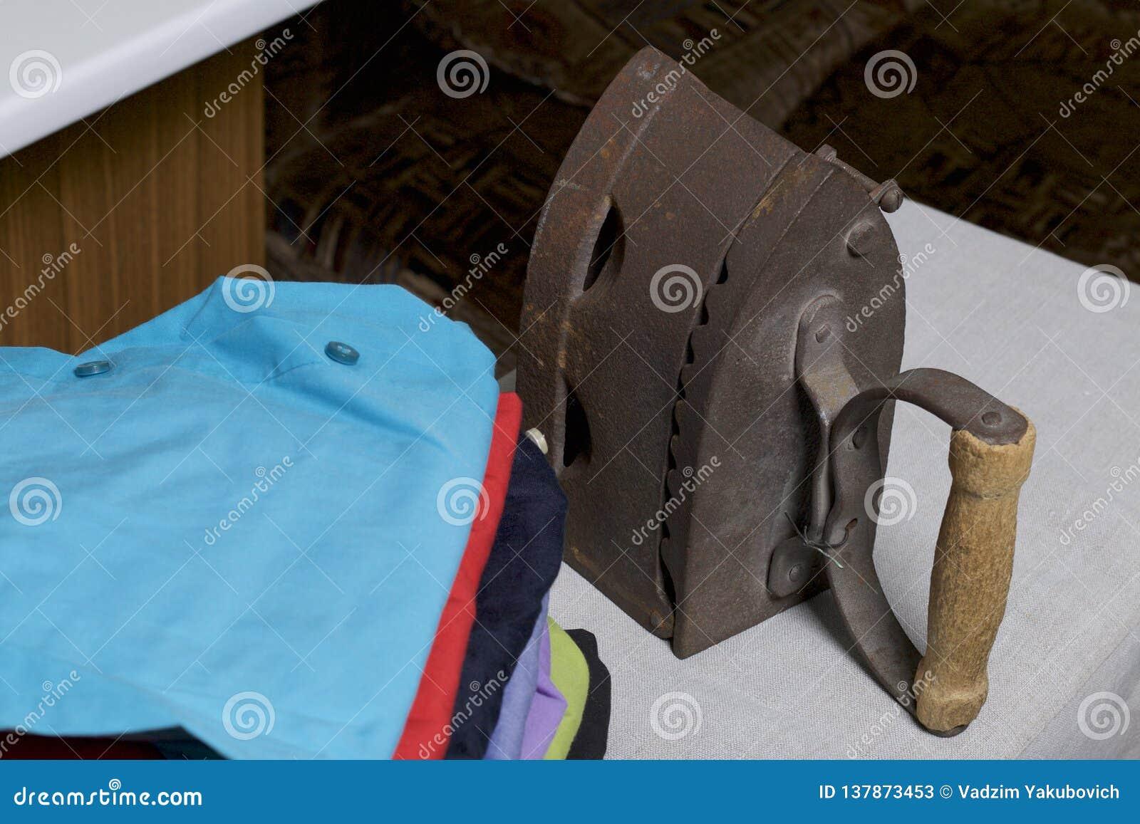 Ferro velho, aquecido por carvões quentes Localizado na tela de linho Estar em uma tábua de passar a ferro Ao lado de uma pilha d