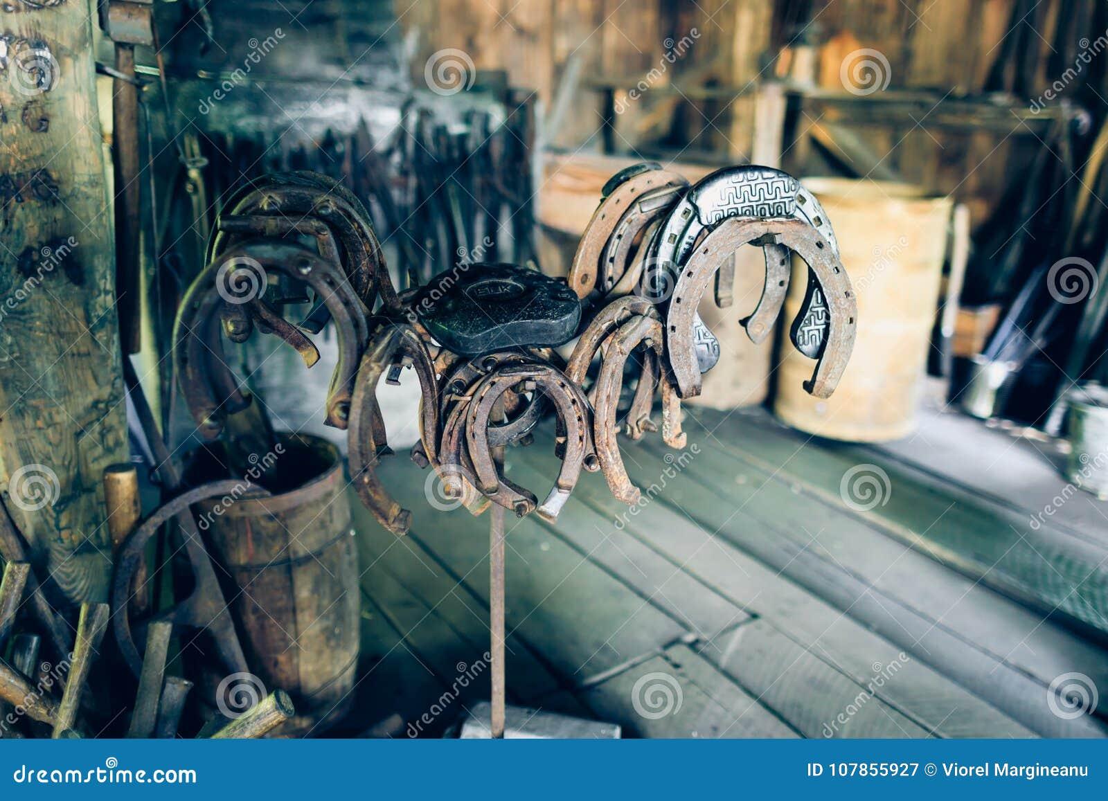 Fers à cheval antiques rouillés de Brown dans une grange