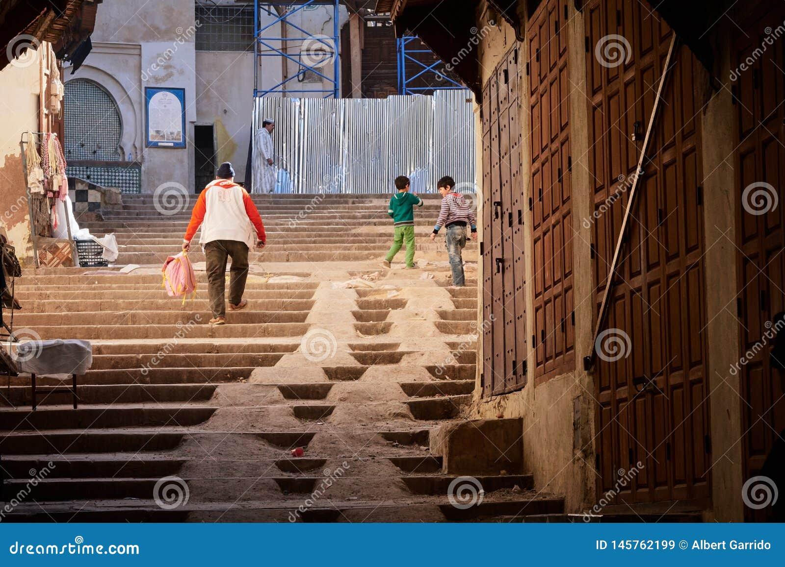 Fes, Marruecos - 7 de diciembre de 2018: niños que juegan en las escaleras en el Medina de Fes