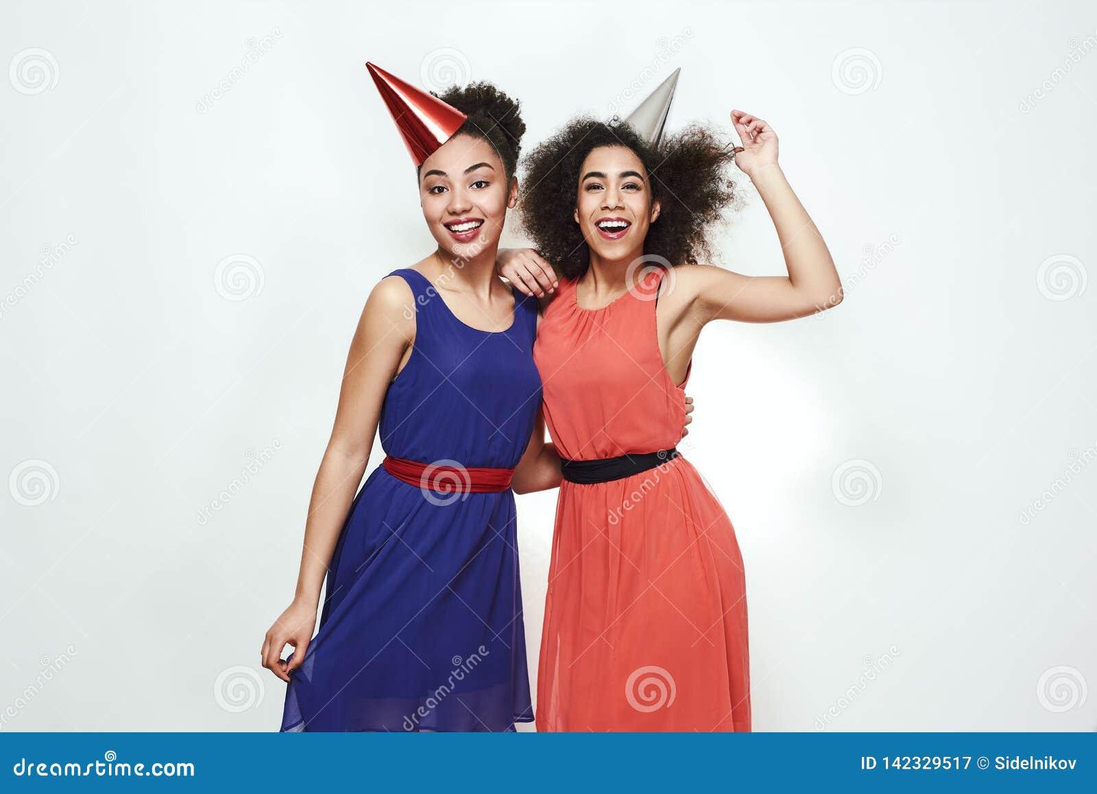 Festa de anos! Dois bonitos e mulheres afro-americanas novas que vestem os vestidos do verão e os chapéus do partido que comemora