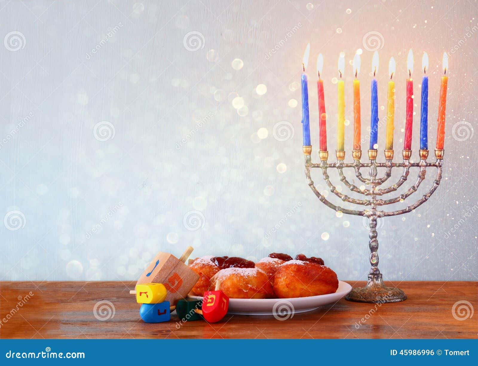 Festa ebrea Chanukah con menorah, ciambelle sopra la tavola di legno retro immagine filtrata