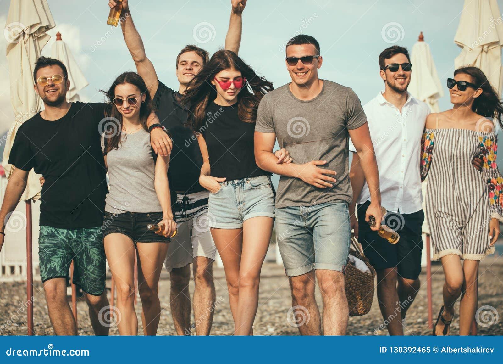 Feste, vacanza gruppo di amici divertendosi sulla spiaggia, sulla camminata, sulla birra della bevanda, sul sorridere e sull abbr