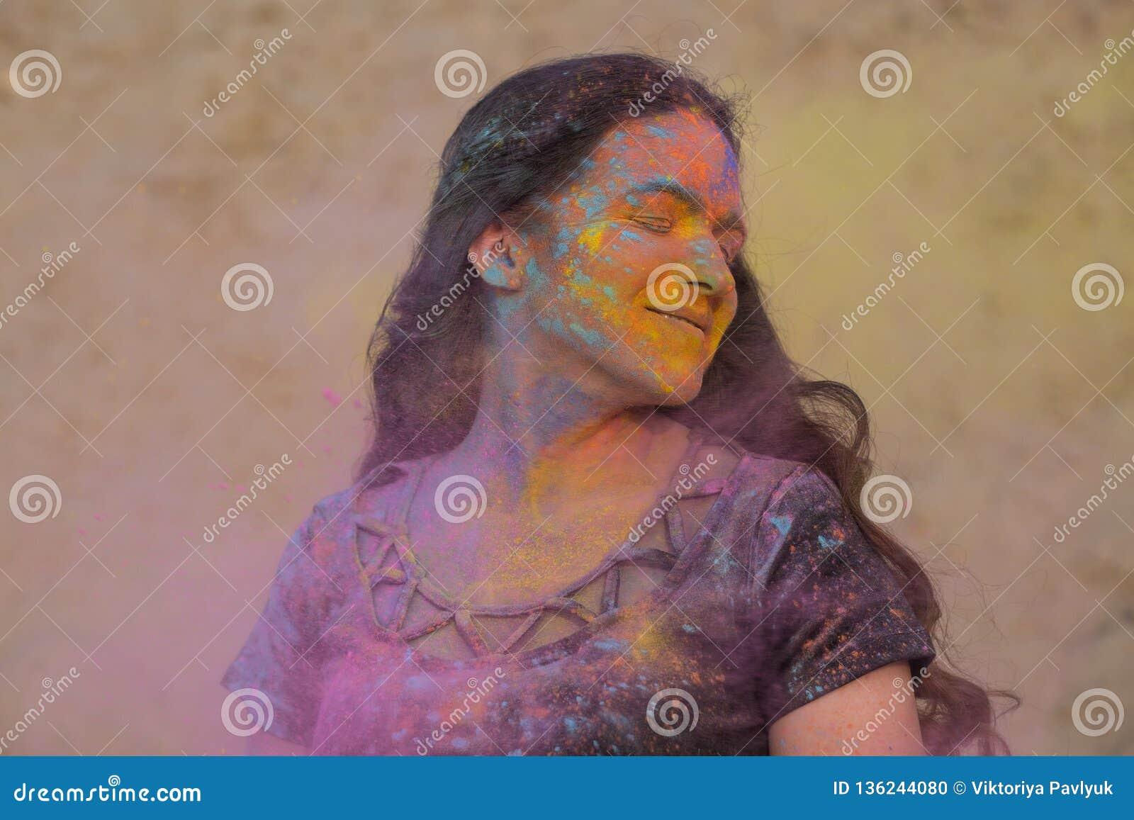 Festival appréciant modèle de Holi de brune heureuse au désert Femme posant avec éclater la peinture sèche