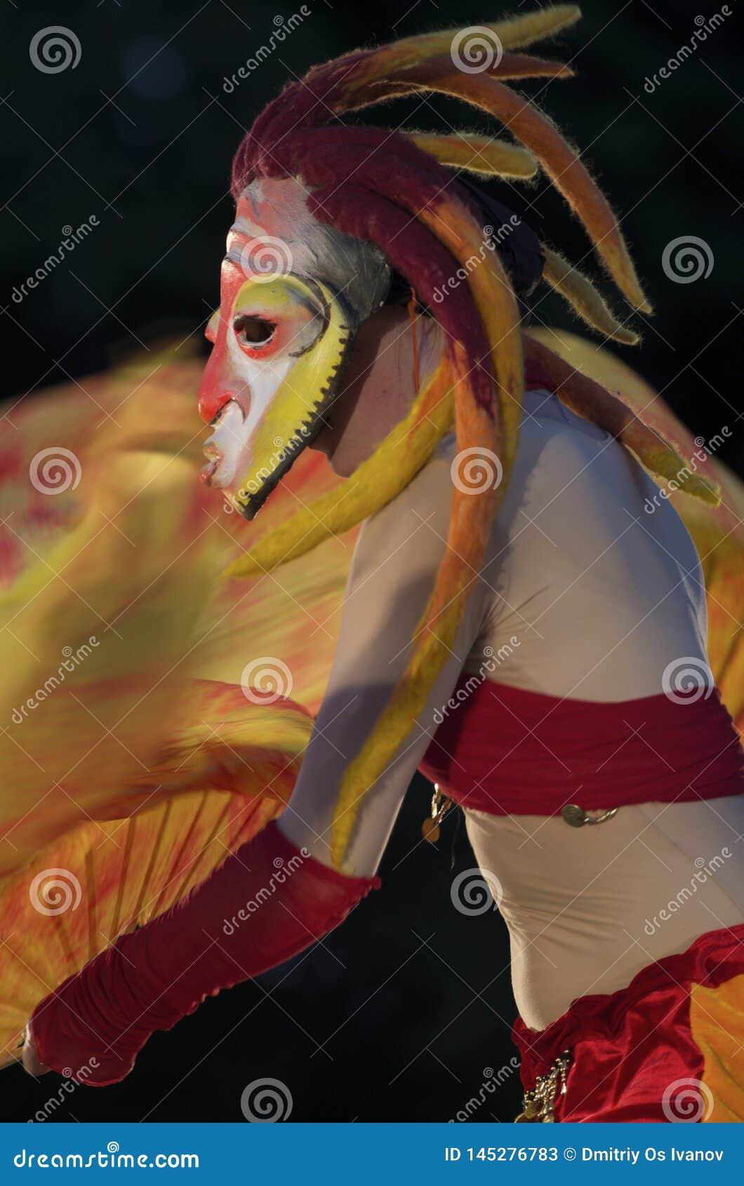 Festival de los teatros 'parque de la calle de Elagin ' Muchacha en una máscara misteriosa con los dreadlocks