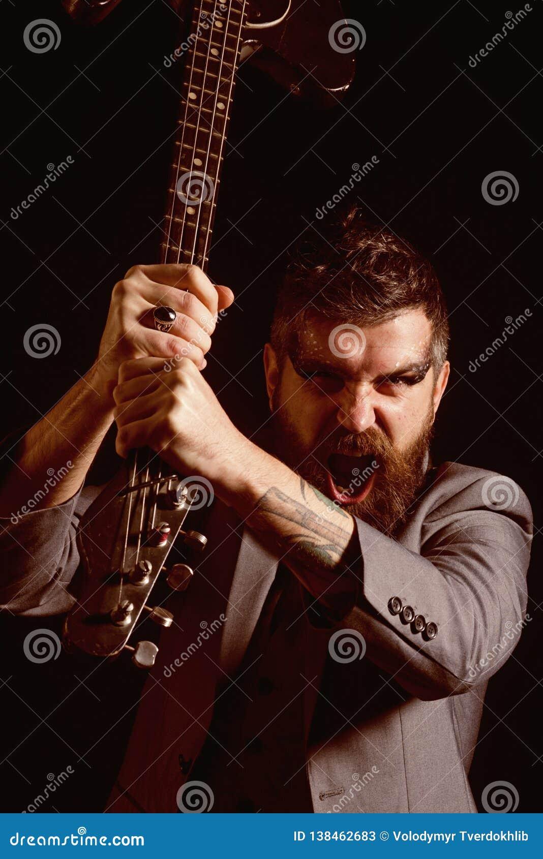 Festival de música Hombre enojado con la guitarra en el festival de música Grito barbudo del hombre en el festival de música Fest